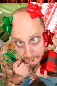 Overwhelmed man wrapping gifts