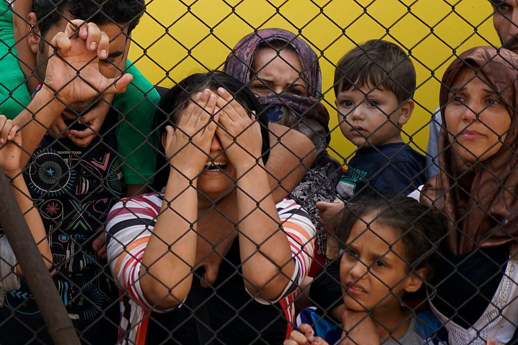 Syrian refugees behind a fence